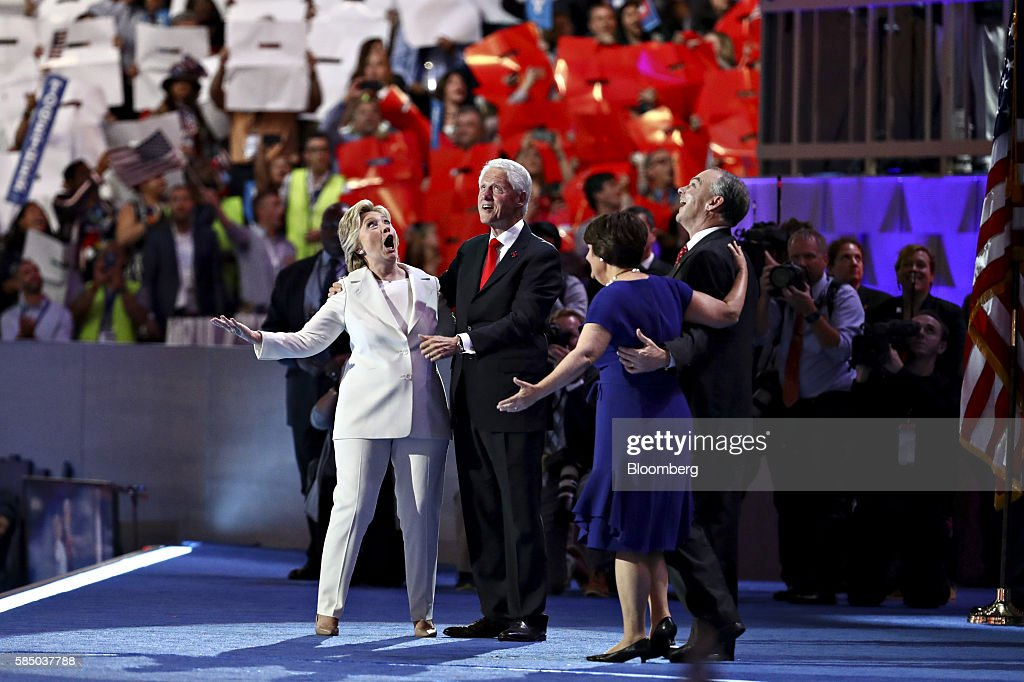 Hillary Clinton, 2016 Democratic presidential nominee, from left, former U.S. President Bill Clinton, Tim Kaine, 2016 Democratic vice presidential nominee, and his wife Anne Holton react on stage during the Democratic National Convention (DNC) in Philadelphia, Pennsylvania, U.S., on Thursday, July 28, 2016. Division among Democrats has been overcome through speeches from two presidents, another first lady and a vice-president, who raised the stakes for their candidate by warning that her opponent posed an unprecedented threat to American diplomacy. Photographer: Andrew Harrer/Bloomberg via Getty Images