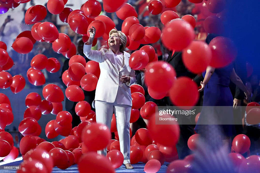 Hillary Clinton, 2016 Democratic presidential nominee, gestures as balloons and confetti fall on stage during the Democratic National Convention (DNC) in Philadelphia, Pennsylvania, U.S., on Thursday, July 28, 2016. Division among Democrats has been overcome through speeches from two presidents, another first lady and a vice-president, who raised the stakes for their candidate by warning that her opponent posed an unprecedented threat to American diplomacy. Photographer: Andrew Harrer/Bloomberg via Getty Images