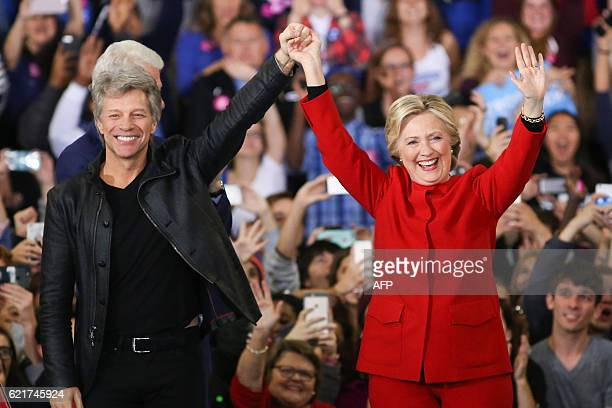 Hillary Clinton and Jon Bon Jovi gesture to the crowd inside the Reynolds Coliseum on the campus of North Carolina State University for the final...