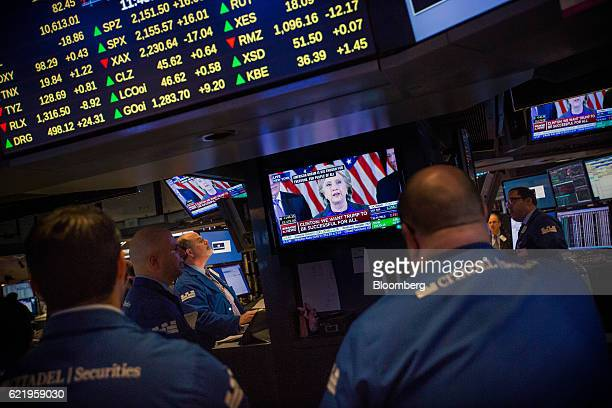 Hillary Clinton former 2016 Democratic presidential nominee is seen speaking on a television while traders work on the floor of the New York Stock...