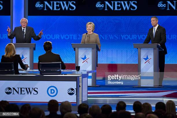 Hillary Clinton former Secretary of State and 2016 Democratic presidential candidate center smiles as Senator Bernie Sanders an independent from...
