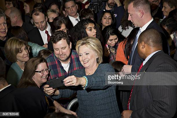 Hillary Clinton former Secretary of State and 2016 Democratic presidential candidate center stands for a selfie photograph with attendees during a...