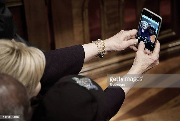 Hillary Clinton former Secretary of State and 2016 Democratic presidential candidate takes a selfie photograph with an attendee during a town hall...
