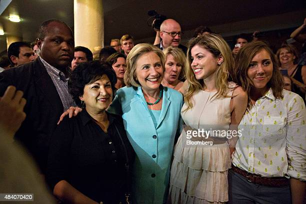 Hillary Clinton former US secretary of state and democratic candidate for US president center poses for a photograph with attendees during the...