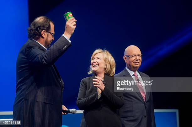 Hillary Clinton, former U.S. Secretary of state, center, smiles as Marc Benioff, chairman and chief executive officer of Salesforce.com Inc., left,...