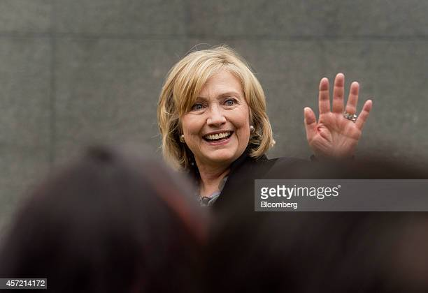 Hillary Clinton, former U.S. Secretary of state, right, waves to attendees during the DreamForce Conference in San Francisco, California, U.S., on...