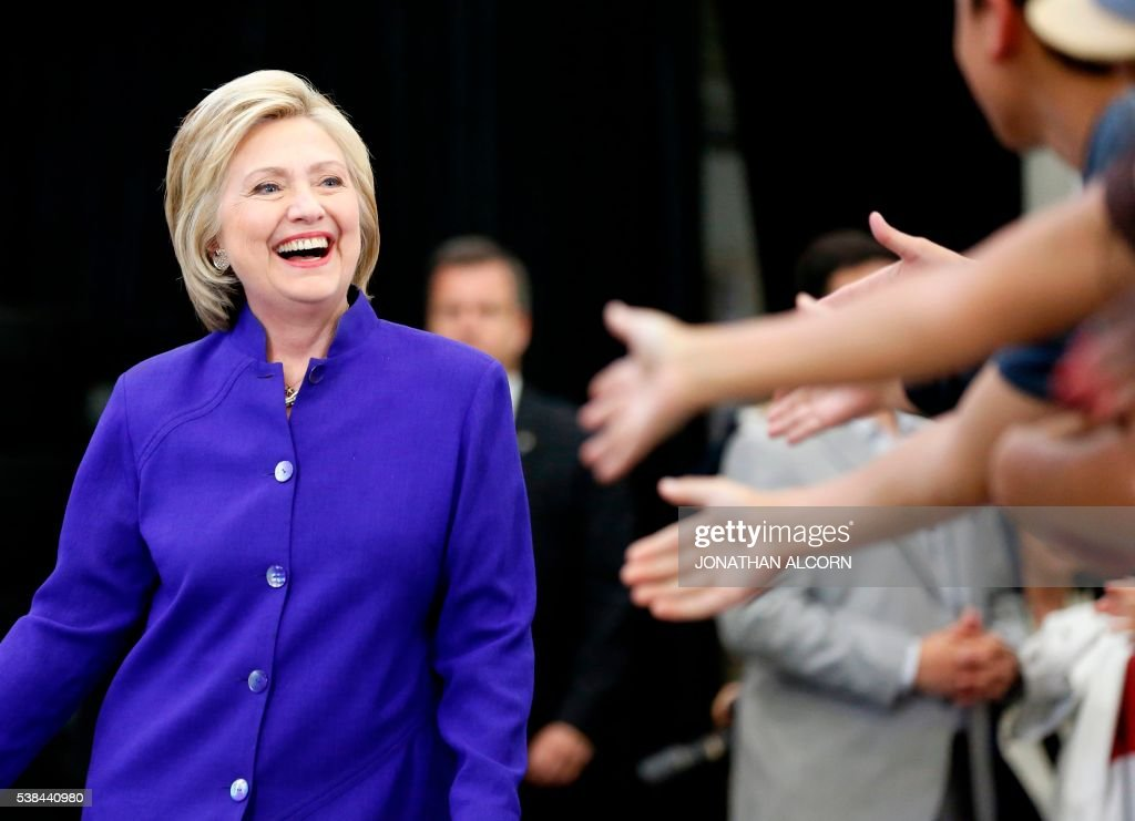 TOPSHOT - Hillary Clinton greets supporters during a rally at Long Beach City College on the final day of California campaigning, June 6, 2016 in Long Beach, California. Hillary Clinton has received commitments from enough delegates to clinch the Democratic presidential nomination, according to the Associated Press and US networks, ensuring she will be the first woman to lead a major US party in the race for the White House. / AFP / JONATHAN