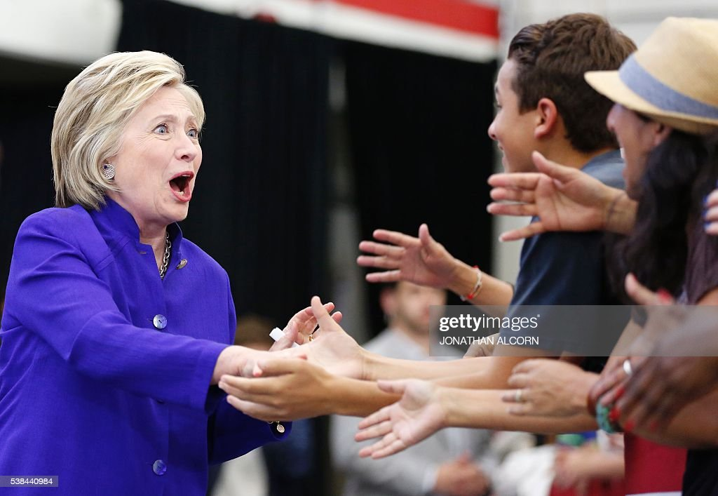 Hillary Clinton greets supporters during a rally at Long Beach City College on the final day of California campaigning, June 6, 2016 in Long Beach, California. Hillary Clinton has received commitments from enough delegates to clinch the Democratic presidential nomination, according to the Associated Press and US networks, ensuring she will be the first woman to lead a major US party in the race for the White House. / AFP / JONATHAN
