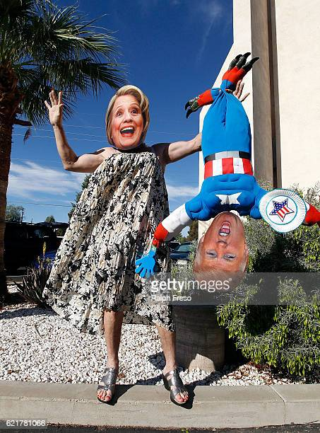 Hillary Clinton supporter Jorge Mendez of Glendale, Arizona wears a dress and Hillary Clinton mask while holding a makeshift doll of Donald Trump...