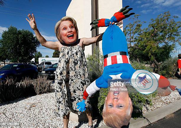 Hillary Clinton supporter Jorge Mendez of Glendale Arizona wears a dress and Hillary Clinton mask while holding a makeshift doll of Donald Trump...