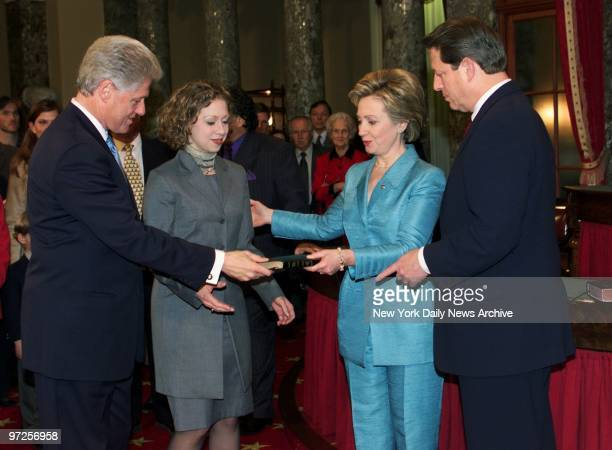 Hillary Rodham Clinton and President Bill Clinton hold bible as daughter Chelsea and Vice President Al Gore look on at recreation of the swearingin...