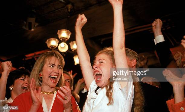 Hillary Rodham Clinton daughter Chelsea cheering for presidential nominee husband/dad Bill Clinton latter raising arms in excitement on floor of...
