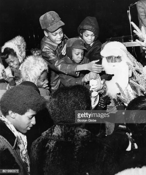 Hilliard Love who is dressed as Santa Claus distributes gifts to children during a multiservice festival sponsored by DorchesterRoxbury SavMor...