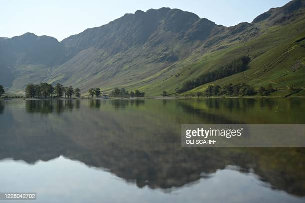 Hills are reflected in the water of Buttermere Lake early in the morning, in the Lake District in north west England on August 14 as many people take...