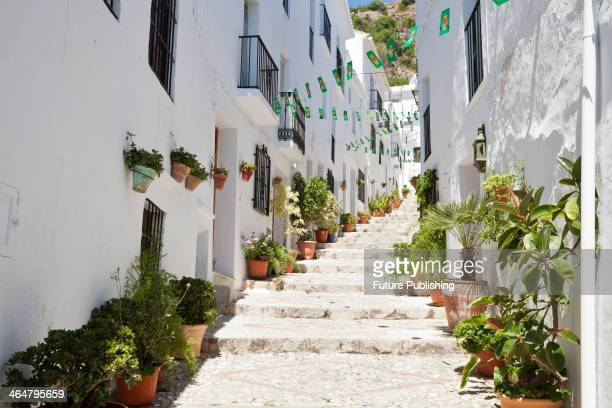 A hillside street with whitewashed buildings and decorative cobblestones in the coastal town of Frigiliana in southern Spain taken on June 13 2013