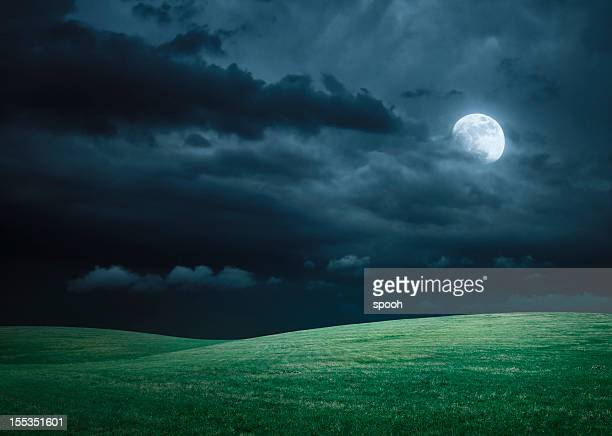 Hilly meadow at night with full moon, clouds and grass