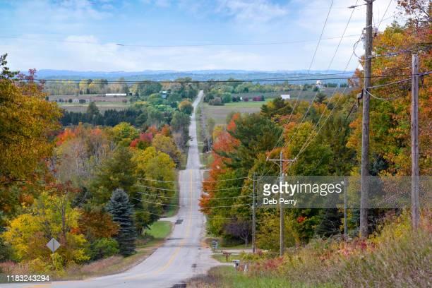 hilly road through autumn color - traverse city fotografías e imágenes de stock