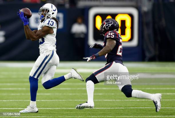 Y Hilton of the Indianapolis Colts catches a pass as he slips behind Kareem Jackson of the Houston Texans during the fourth quarter at NRG Stadium on...