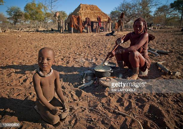 Himba Boy With His Mother Preparing The Meal in Village Of Karihona Namibia on August 08 2010 Himbas are a bantu ethnic group These nomadic...
