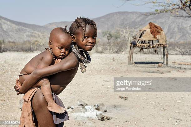 Himba child carrying her sister on her back