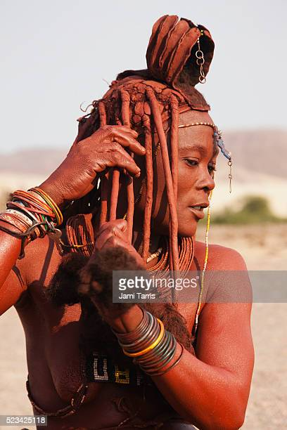 a himba girl mixes ochre and fat to apply to her exposed skin and hair - himba stock-fotos und bilder