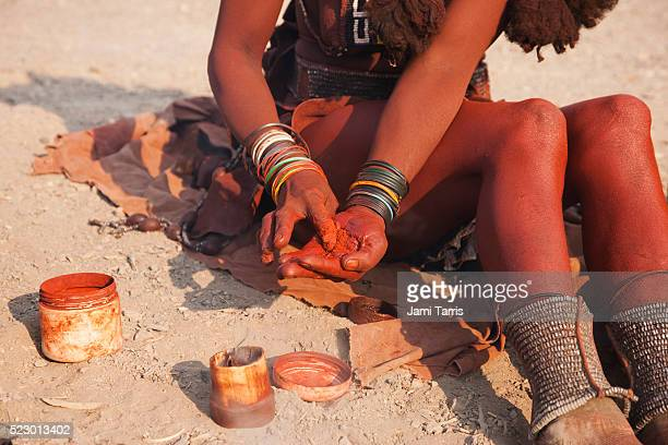 a himba girl mixes ochre and fat to apply to her exposed skin - himba stock-fotos und bilder