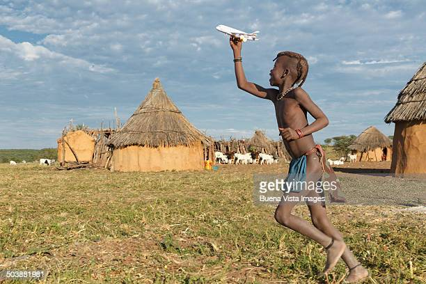 himba girl playing wit a toy airplane - himba foto e immagini stock
