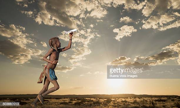 Himba girl playing wit a toy airplane