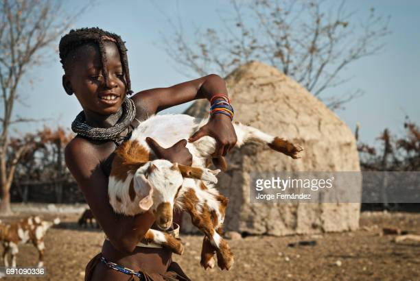Himba girl with a goat in a village of mud huts