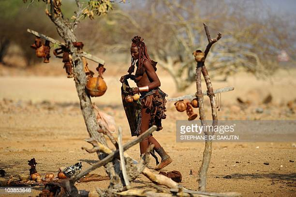 A Himba woman arranges souvenirs to sell to tourists on August 20 2010 in the village of Okapare near Opuwo in northern Namibia AFP PHOTO / STEPHANE...
