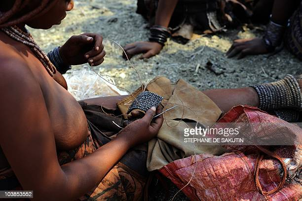 A Himba woman makes a traditional bracelet on August 19 2010 in the village of Ohungumure 15 kms west of Opuwo in northern Namibia AFP PHOTO /...