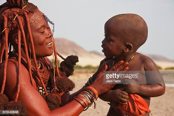 a himba woman mixes ochre and fat to apply to exposed skin and hair for beauty and sun protection - himba stock-fotos und bilder