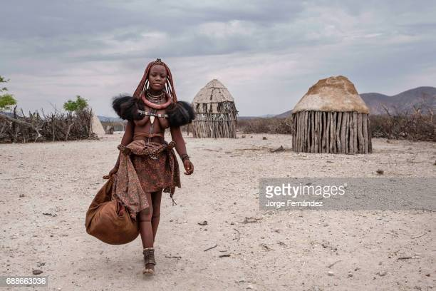 Himba woman ready to travel with her belongings in a village near Epupa falls. Himbas are a bantu tribe who migrated into what today is Namibia a few...
