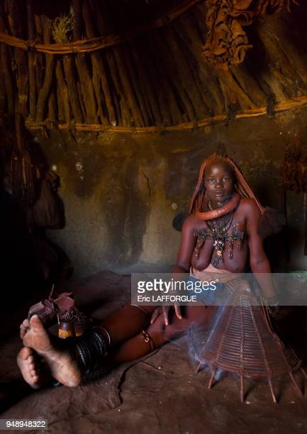 Himba woman using incense to purify herself and her clothes epupa Namibia on March 3 2014 in Epupa Namibia