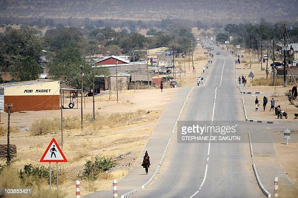 A Himba woman walks on August 21 2010 on the main street of Opuwo in northern Namibia AFP PHOTO / STEPHANE DE SAKUTIN