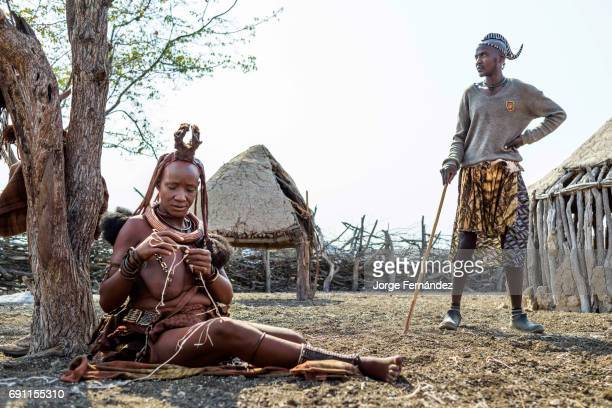 Himba woman weaving plastic threads made out of old plastic bags Young himba man with traditional scorpion tail in the background