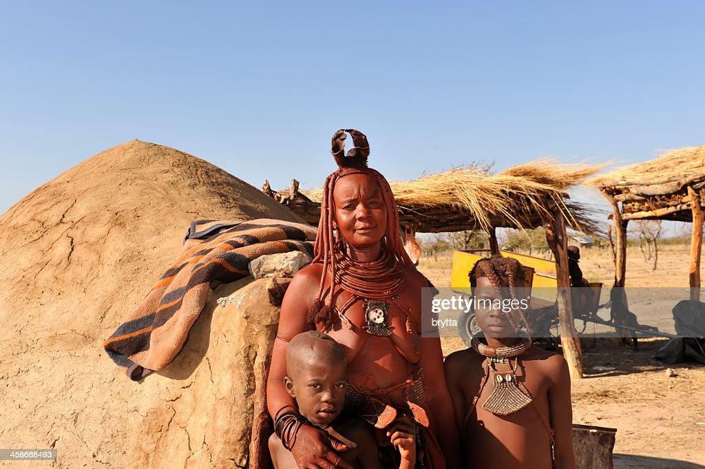 Himba woman with children standing near hut , Opuwo,Namibia : Stock Photo