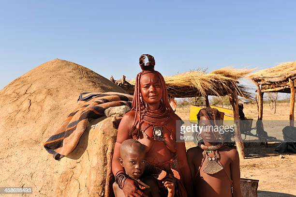 himba woman with children standing near hut , opuwo,namibia - opuwo tribe stock photos and pictures