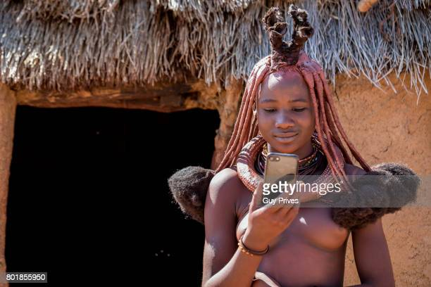 Himba woman with traditional hair dress using an iphone