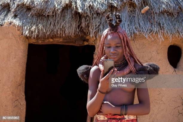 himba woman with traditional hair dress using an iphone - himba photos et images de collection