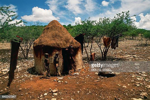 Himba woman with two children in front of their hut in a village, Damaraland Wilderness Area, Namibia.