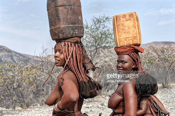 Himba women carrying water on their heads