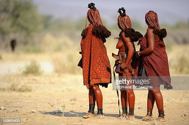 Himba women look on August 19 2010 at a car arriving on the road between Ohungumure and Opuwo in northern Namibia AFP PHOTO / STEPHANE DE SAKUTIN