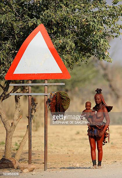 A Himba's woman holds her baby as she waits by the road for a car to take her to town on August 19 2010 in Ohungumure Opuwo northern Namibia AFP...