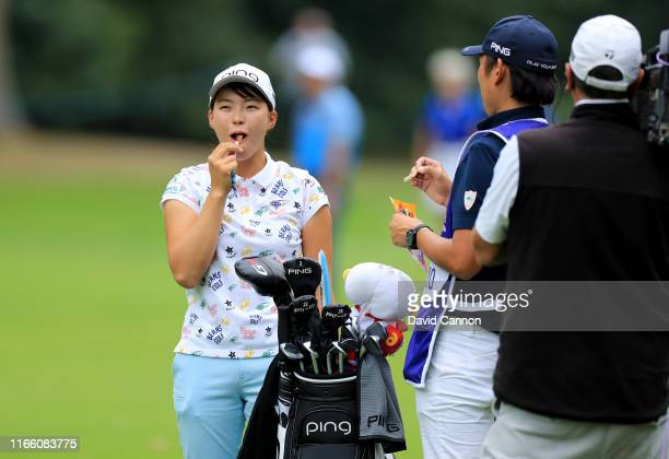 Hinako Shibuno of Japan eats a snack before she played her second shot on the par 4 16th hole during the final round of the AIG Women's British Open...