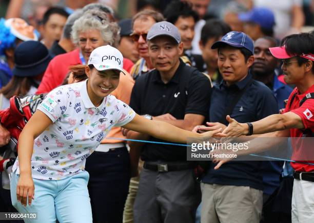 Hinako Shibuno of Japan greets spectators as she walks to the 16th tee during Day Four of the AIG Women's British Open at Woburn Golf Club on August...