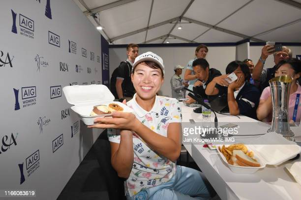 Hinako Shibuno of Japan poses for a photo with a cake during a press conference during Day Four of the AIG Women's British Open at Woburn Golf Club...