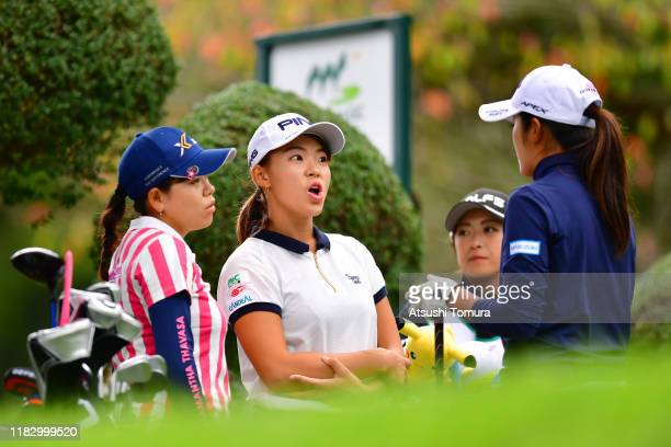 Hinako Shibuno of Japan reacts after adjusting a collar of Mone Inami with Minami Katsu on the 12th tee during the first round of the Nobuta Group...