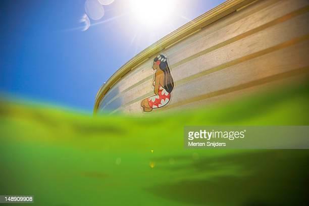 hinano beer logo sticker of polynesian woman on boat floating in lagoon. - merten snijders stockfoto's en -beelden