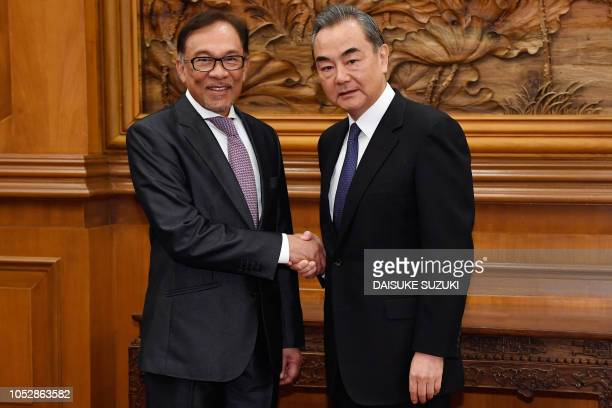 Çhina's Foreign Minister Wang Yi shakes hands with Malaysia's People's Justice Party president and leader of the Pakatan Harapan coalition Anwar...
